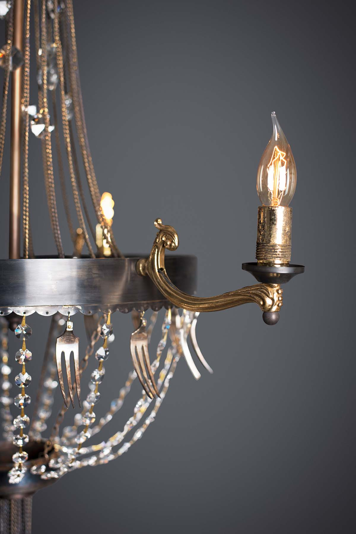 detail of Ambrosia small chandelier made from Recycled materials and vintage cutlery. In an antique finish.